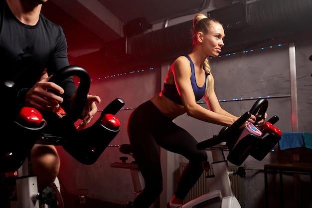 Groep sportieve mensen in de sportschool, perfect gevormde gespierde mensen trainen op de fiets, cardiotraining in de fitnessruimte, gewichtsverlies met machine nemen