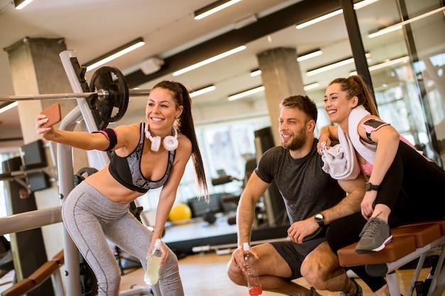 Groep sportieve mensen in sportkleding die selfie foto met mobiele telefoon nemen bij gymnastiek