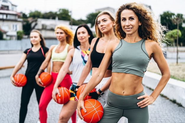 Groep sportieve vrouwen die oefeningen met oranje ballen uitvoeren