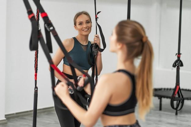 Groep sportieve vrouwen die trainen met trx-fitnessapparatuur met trainer in de buurt