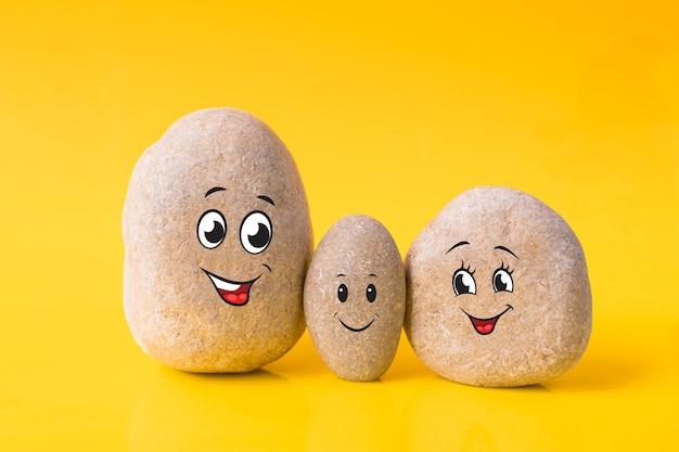 Groep stenen met getekende grappige gezichten op gele achtergrond. vader, moeder en zoon. concept van gelukkige familie.
