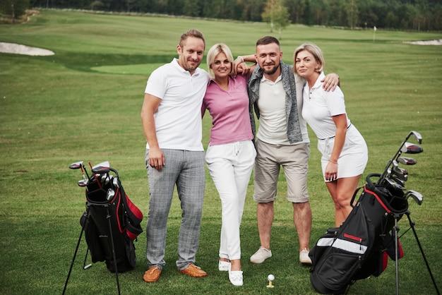Groep stijlvolle vrienden op de golfbaan leren een nieuw spel te spelen. het team gaat rusten na de wedstrijd