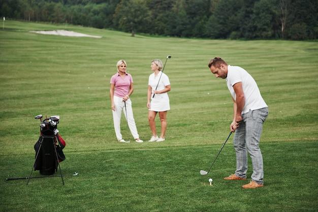 Groep stijlvolle vrienden op de golfbaan leren een nieuw spel te spelen