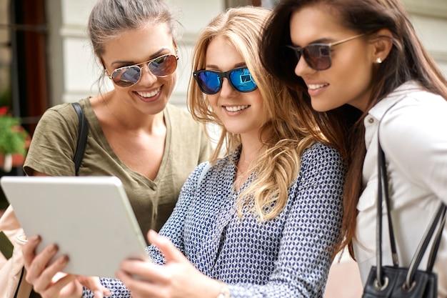 Groep stijlvolle vrouwen die genieten in de stad en een digitale tablet gebruiken