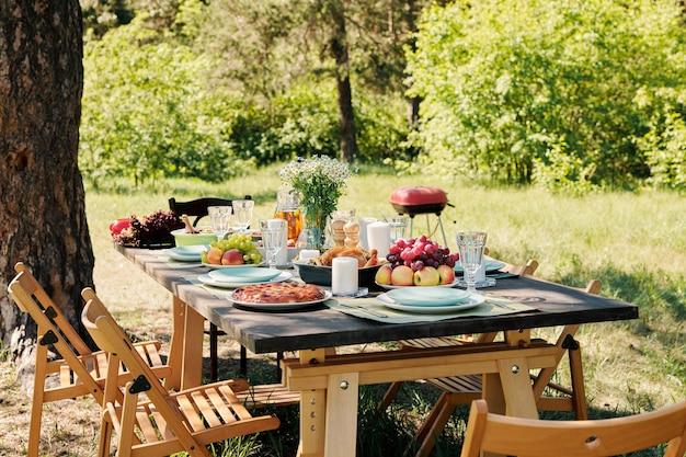 Groep stoelen rond houten geserveerd feestelijke tafel met zelfgemaakt eten en drinken, vers fruit en bloemen onder dennenboom op zonnige dag