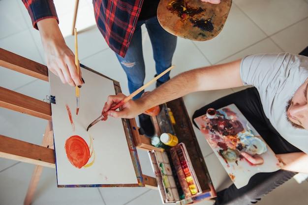 Groep studenten die bij kunstlessen schilderen