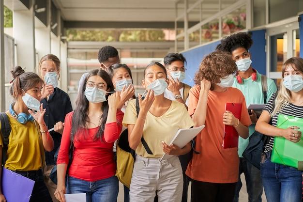 Groep studenten die hun gezichtsmaskers opzetten of afdoen, jongeren van verschillende etniciteiten nemen...