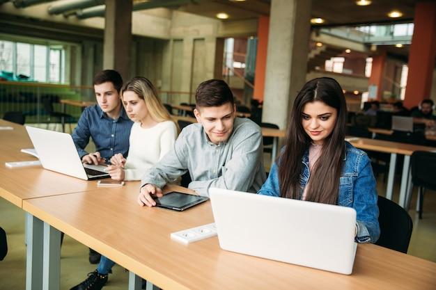 Groep studenten die in de schoolbibliotheek studeren, een meisje en een jongen gebruiken laptop en