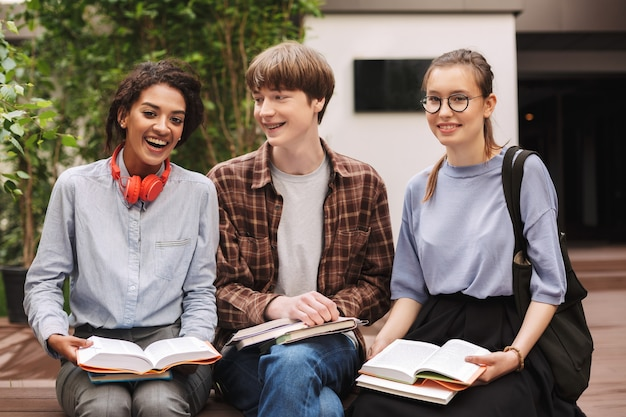 Groep studenten die op bank met boeken zitten en gelukkig