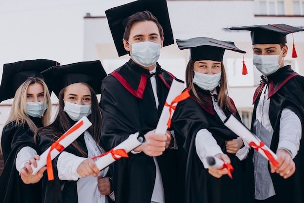 Groep studenten die samen afstuderen vieren en gezichtsmaskers dragen