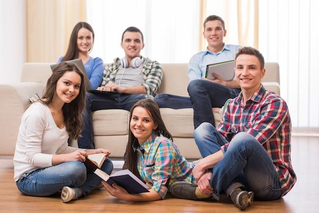 Groep studenten met boeken en laptop.