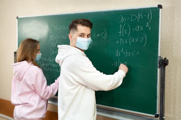 Groep studenten met gezichtsmasker die tijdens pandemie op het bord in de klas schrijven