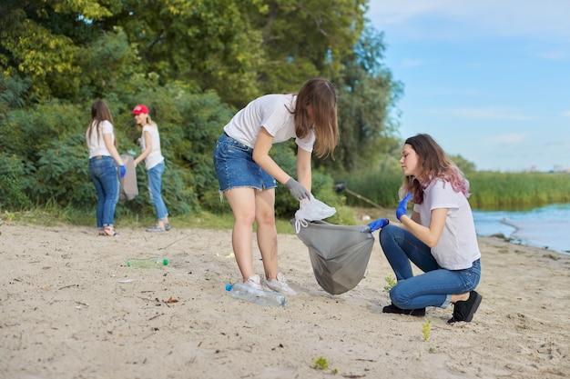 Groep studenten met leraar in de natuur die plastic afval opruimen. milieubescherming, jeugd, vrijwilligerswerk, liefdadigheid en ecologie concept
