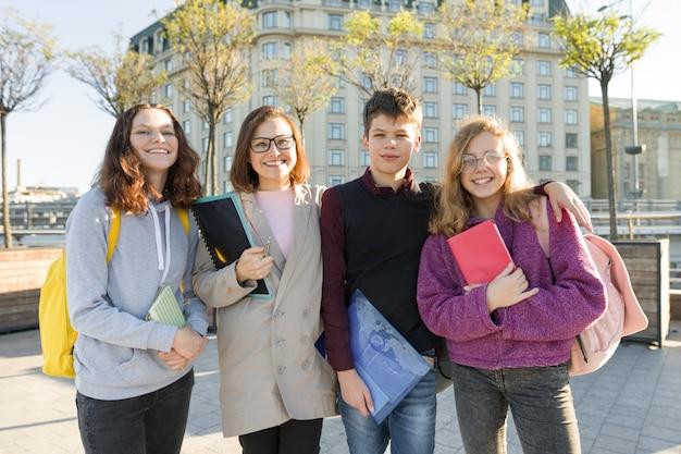 Groep studenten met leraar, tieners praten met vrouwelijke leraar