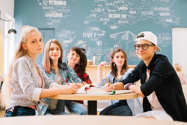 Groep studenten poseren aan tafel