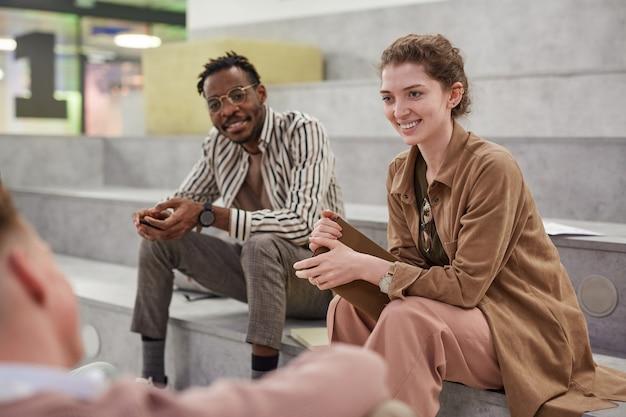 Groep studenten vrolijk aan het kletsen terwijl ze ontspannen in de moderne schoollounge, focus op lachende jonge vrouw die met een vriend praat