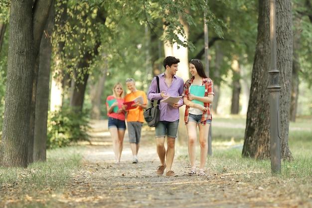 Groep studenten wandelen langs het steegje stadspark. foto met kopie ruimte.