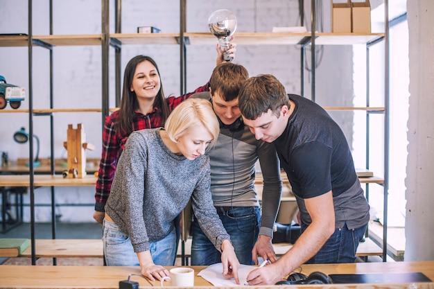Groep studentenvrienden doen en bespreken creatieve ideeën in het hok