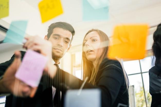 Groep succesvol zakelijk groepswerk. brainstormvergadering met kleurrijke kleverige papieren notitie op glazen wand voor nieuwe ideeën.