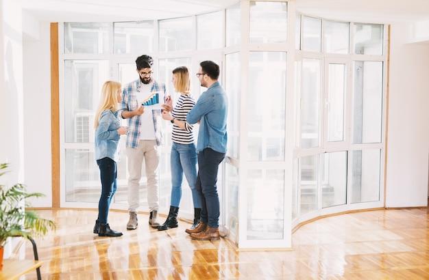Groep succesvolle creatieve jonge bedrijven kijken naar grote vooruitgang op de grafiek in het heldere kantoor.