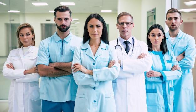 Groep succesvolle en zelfverzekerde moderne artsen poseren en kijken op de camera naar de ziekenhuisgang