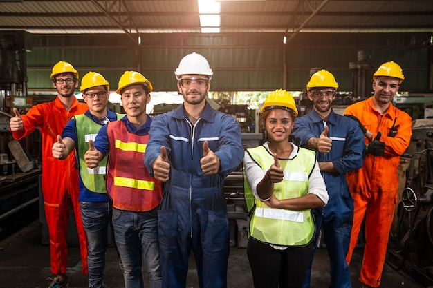 Groep team worker mix race genieten van het werken in een zware fabriek staan samen glimlachend gelukkige hand duimen opdagen