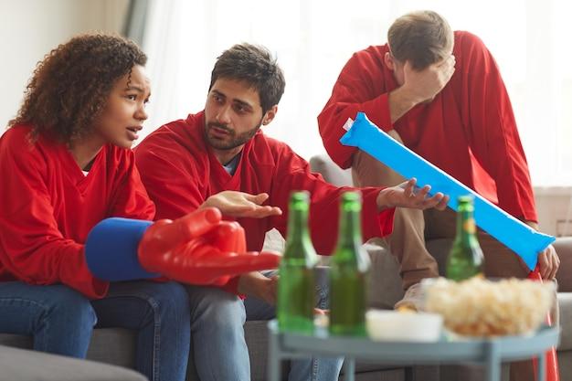 Groep teleurgestelde fans kijken naar sportwedstrijd op tv thuis en bespreken verliezende beweging terwijl ze rode teamuniformen dragen