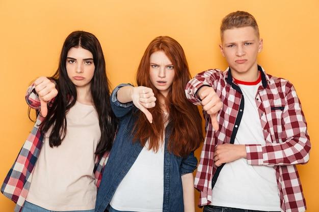 Groep teleurgestelde schoolvrienden die duimen tonen
