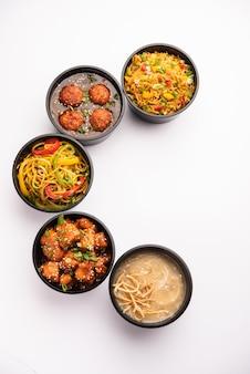 Groep thuisbezorgd indo-chinees eten in plastic verpakkingen, containers of dozen met schezwan-noedels, gebakken rijst, chili-kip, manchurian en soep.
