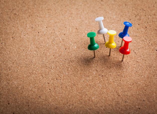 Groep thumbtacks die op corkboardbackground wordt gespeld