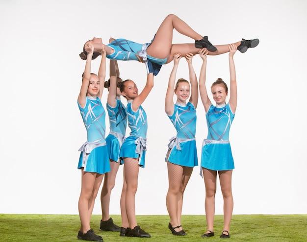Groep tiener cheerleaders die op wit stellen