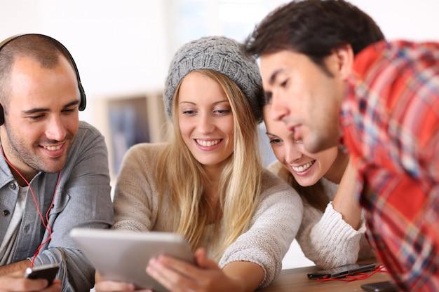 Groep tienerjaren die digitale technologieën gebruiken