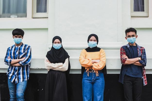 Groep tienerjaren met het leunen op muur en gevouwen wapens die maskers dragen