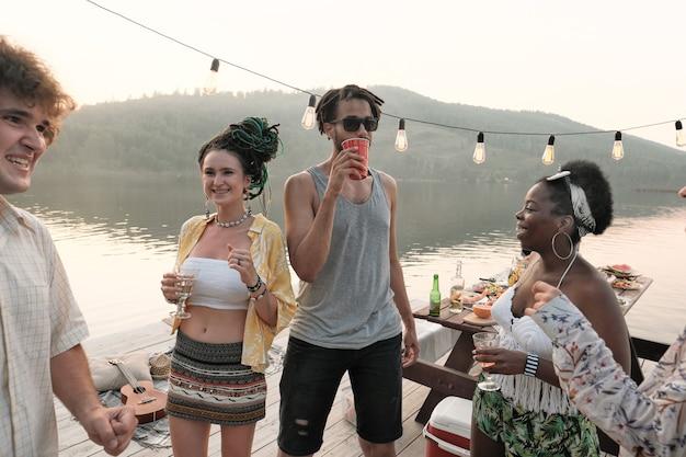 Groep tieners cocktails drinken en plezier hebben op een feestje buiten