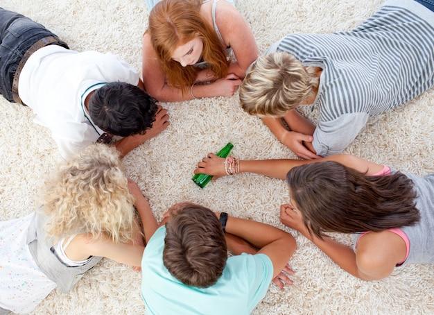 Groep tieners die met een fles op de vloer spelen