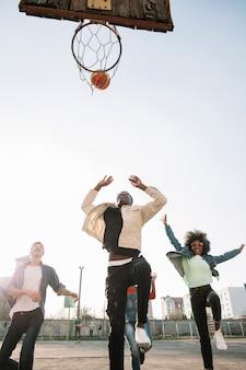 Groep tieners die samen basketbal spelen