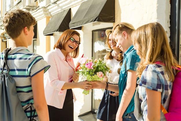Groep tieners feliciteren hun leraar