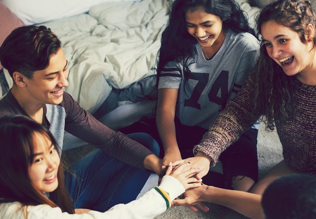 Groep tieners in een slaapkamer samenstellen van hun handen