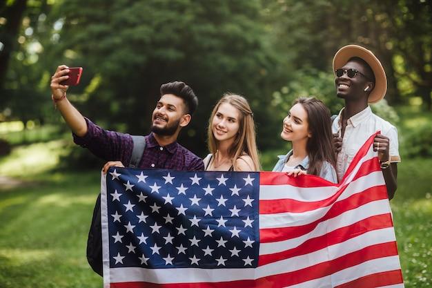 Groep tieners maakt een selfie met amerikaanse vlag die 4 juli viert