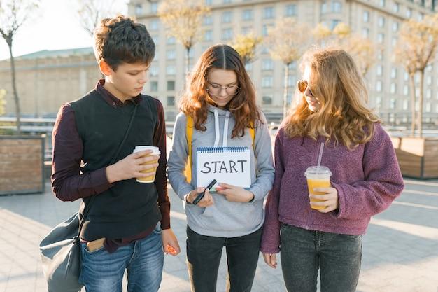 Groep tieners met kladblok met handgeschreven woord start