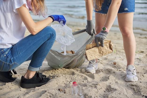 Groep tieners op rivieroever die plastic afval in zakken oppakken. milieubescherming, jeugd, vrijwilligerswerk, liefdadigheid en ecologie concept