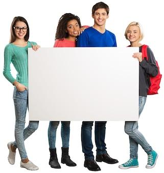 Groep tienerstudenten die witte lege banner houden die op witte achtergrond wordt geïsoleerd
