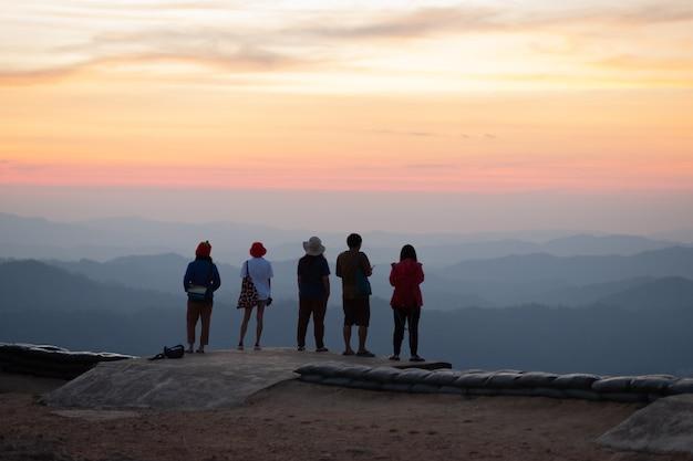Groep toeristen die zich voor de zonsondergang bevinden. op nern chang suek, kanchanaburi in thailand.