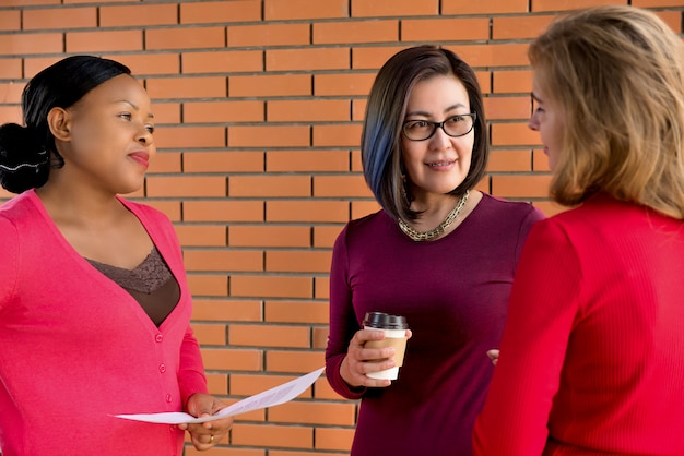 Groep toevallige multi-etnische vrouwen die en hun vriend luisteren machtigen