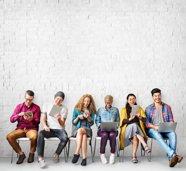 Groep uiteenlopende mensen maakt gebruik van digitale apparaten