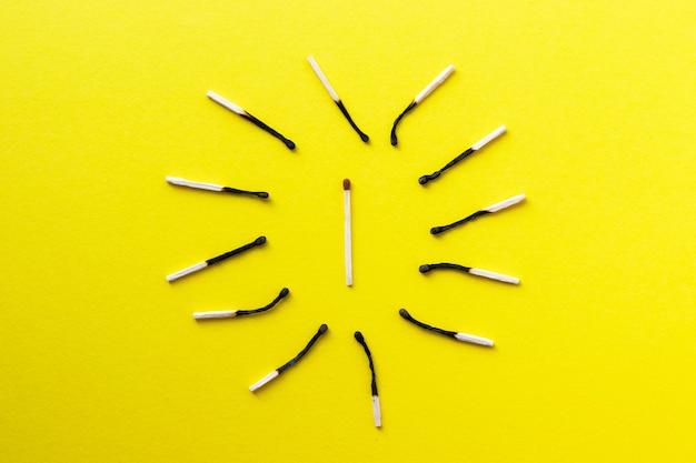 Groep uitgebrande en één ongebruikte lucifer op geel