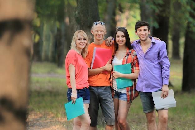 Groep universitaire studenten die buiten gelukkig kijken.