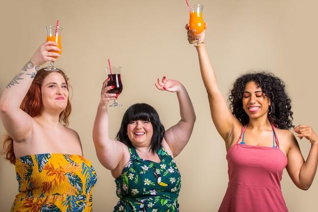 Groep van 3 overmaatse vrouwen die in studio stellen