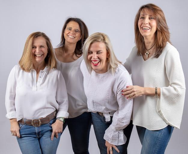 Groep van 4 vrouwen, vrienden van middelbare leeftijd die lol hebben in een fotosessie