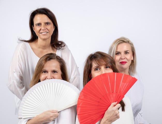 Groep van 4 vrouwen, vrienden van middelbare leeftijd die plezier hebben in een fotosessie, zittend op een bal en spelen met een ventilator